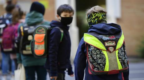 Unter Einhaltung der Abstandsregeln und mit Mund-Nasen-Schutz warten Kinder am 7. Mai 2020 vor einer Grundschule in Dortmund. Mit dem Start des neuen Schuljahres gilt in ganz Nordrhein-Westfalen Maskenpflicht an allen Schulen.