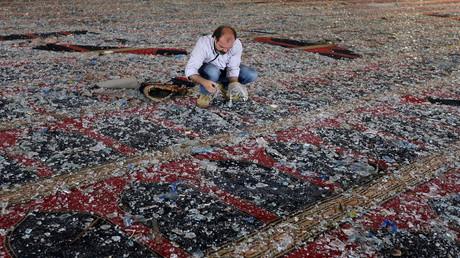 Ein Mann entfernt Glasscherben auf dem Teppich einer Moschee, die bei der Explosion am Dienstag in Beirut beschädigt wurde.