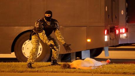 Ein Strafverfolgungsbeamter gestikuliert neben einem auf dem Boden liegenden Mann bei Zusammenstößen mit Oppositionsanhängern nach dem Wahlschluss bei den Präsidentschaftswahlen in Minsk, Belarus. 9. August 2020.
