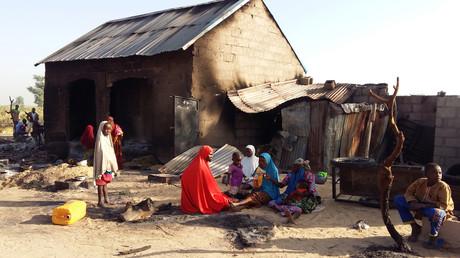 Menschen sitzen nach einem Angriff mutmaßlicher Mitglieder der islamistischen Boko Haram im Dorf Bulabulin in Nigeria in der Nähe eines niedergebrannten Hauses.