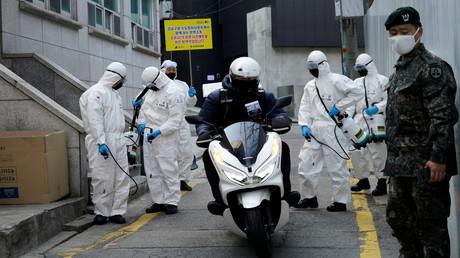 Südkoreanische Soldaten in Schutzkleidung desinfizieren eine Straße in einem Einkaufsviertel in Seoul