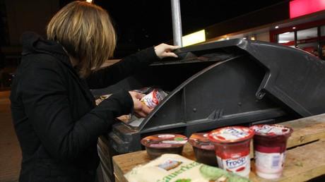 Symbolbild: Eine Frau sucht bei Nacht nach Lebensmitteln in einem Müllcontainer eines Supermarktes. (Berlin, 09. Juni 2006)