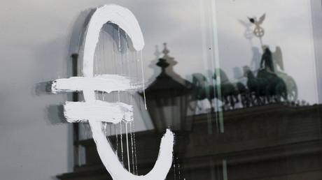 Das Zeichen der Euro-Währung ist auf eine Glastür gemalt, auf der sich das Brandenburger Tor spiegelt.