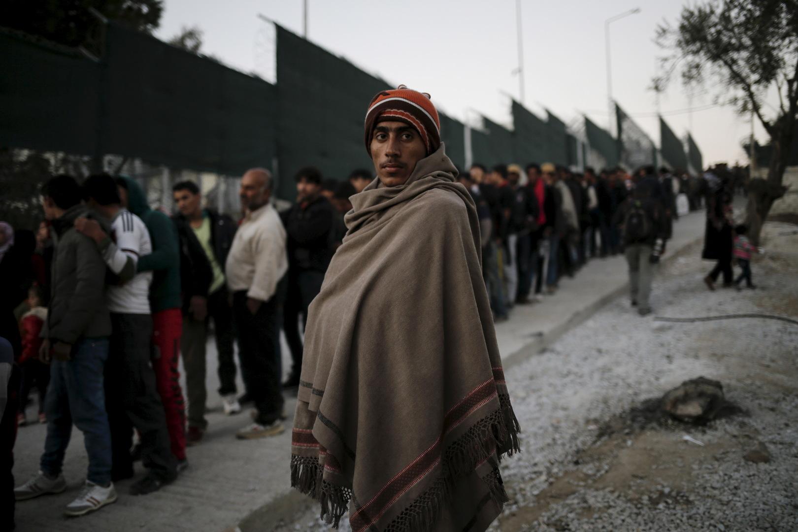 Ein Migrant wird mit einer Decke zugedeckt, während sich Flüchtlinge und Migranten im Flüchtlingslager Moria auf der griechischen Insel Lesbos für eine Lebensmittelverteilung anstellen. 5. November 2015