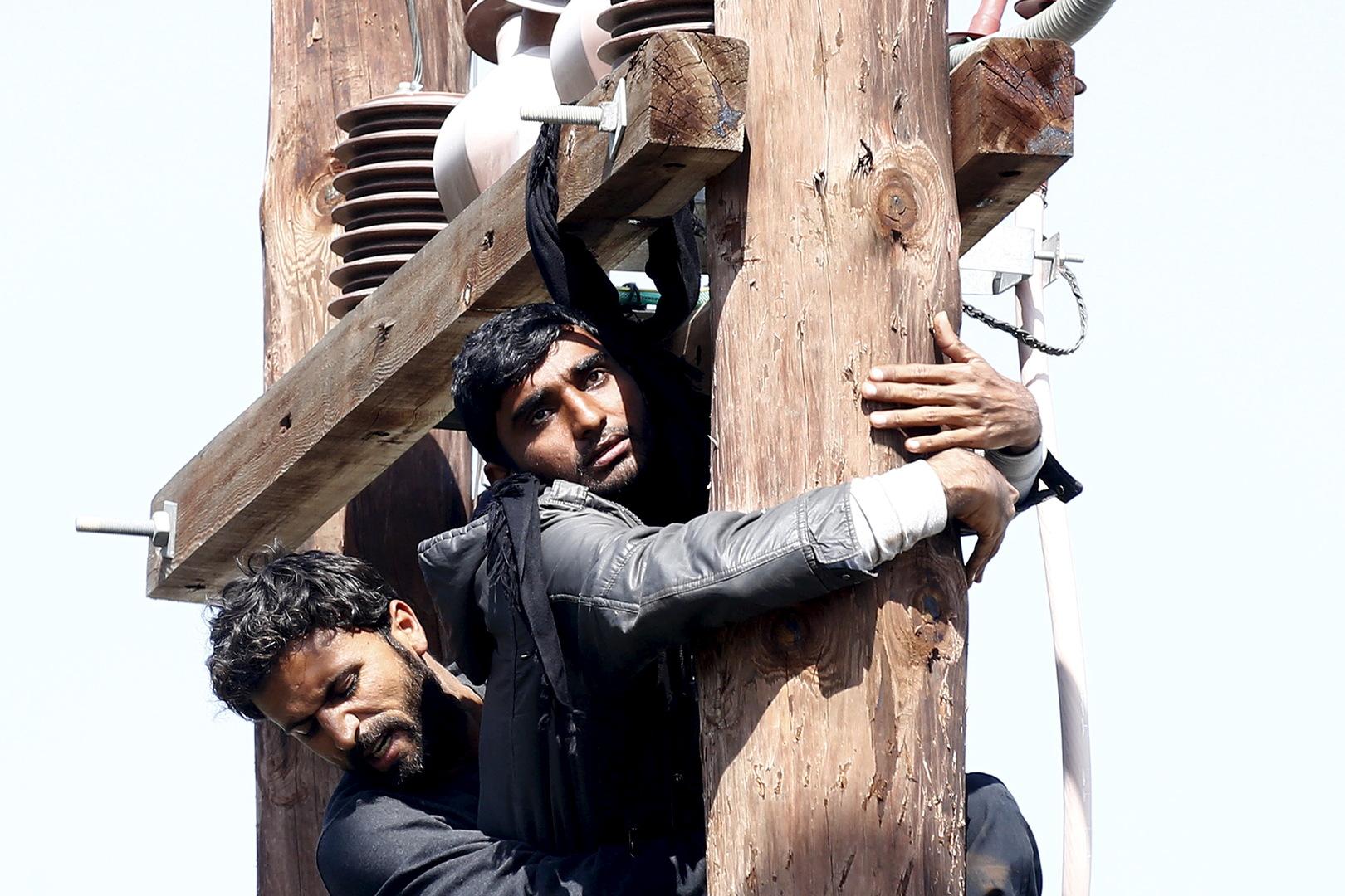 Ein pakistanischer Migrant (Front) droht, sich an einem Strommast zu erhängen, während ein anderer versucht, ihn während einer Demonstration im Registrierungszentrum von Moria auf der griechischen Insel Lesbos am 6. April 2016 festzuhalten.