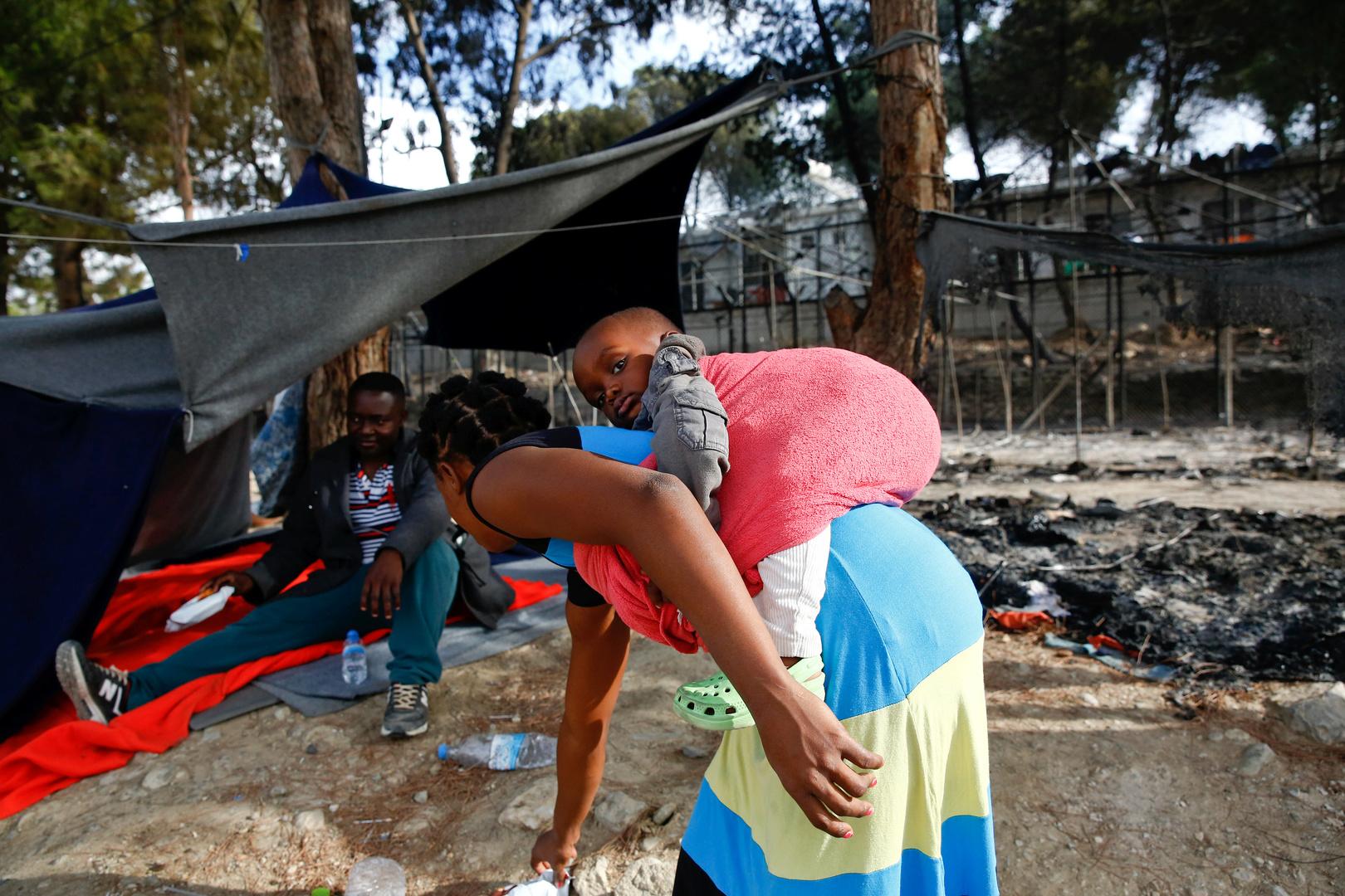 Eine Migrantin trägt ein Baby bei sich, als sie neben den Überresten eines abgebrannten Zeltes im Migrantenlager Moria steht, nachdem ein Feuer auf der Insel Lesbos, Griechenland, bei Gewalttätigkeiten unter den Bewohnern Zelte zerrissen und Container zerstört hatte. 20. September 2016.