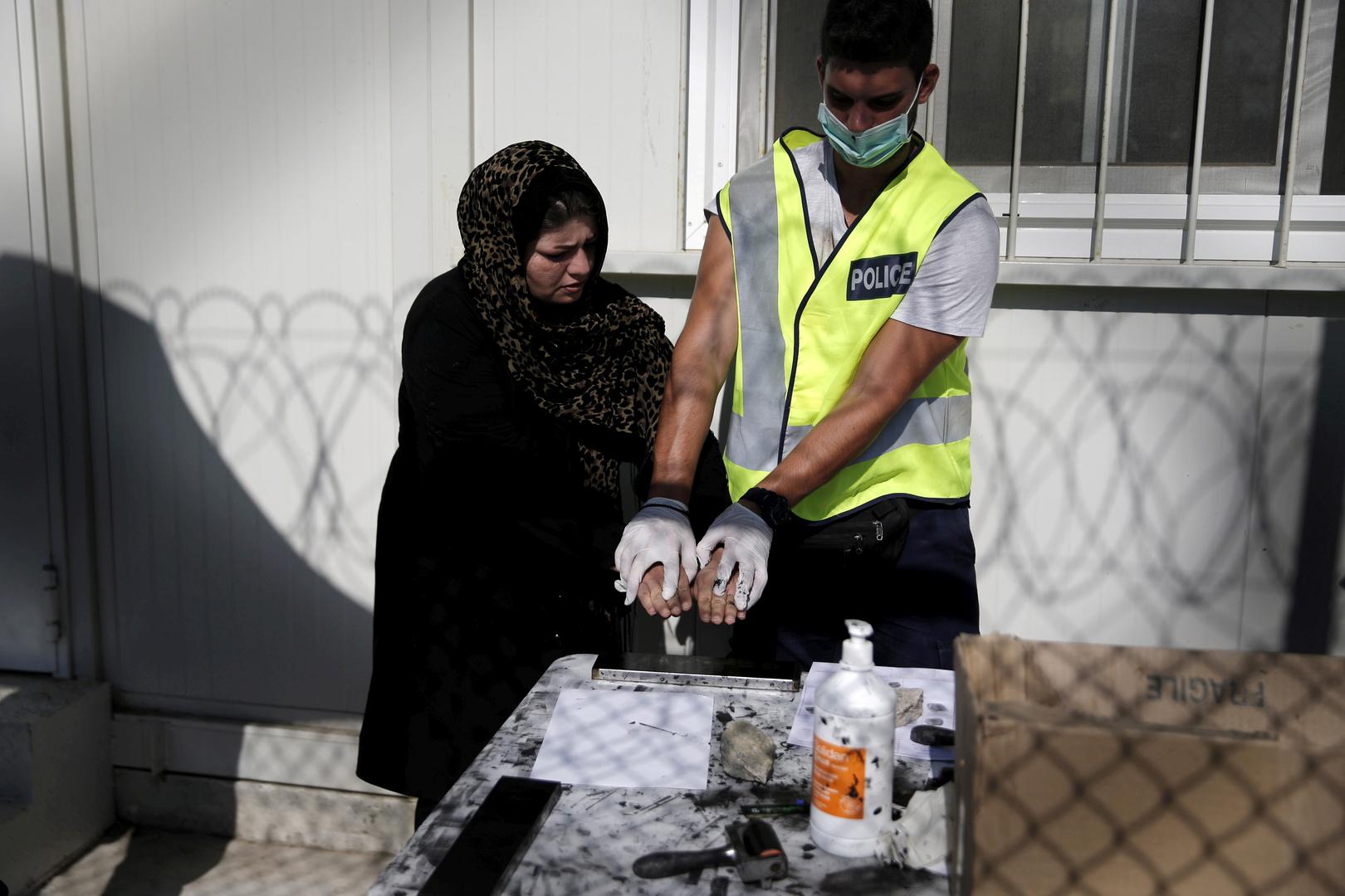 Ein afghanischer Flüchtling lässt sich von einem Polizeibeamten während eines Registrierungsverfahrens im Flüchtlingslager in der Nähe des Dorfes Moria auf der griechischen Insel Lesbos ihre Fingerabdrücke abnehmen. 13. September 2015.