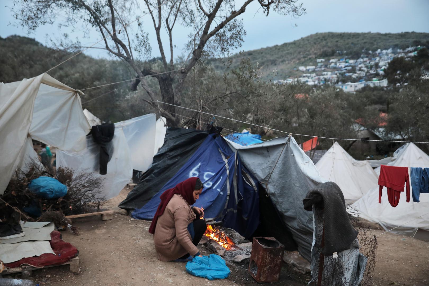 Eine Frau entzündet ein Feuer in einem provisorischen Lager für Flüchtlinge und Migranten neben dem Lager Moria auf der Insel Lesbos, Griechenland, 7. März 2020.