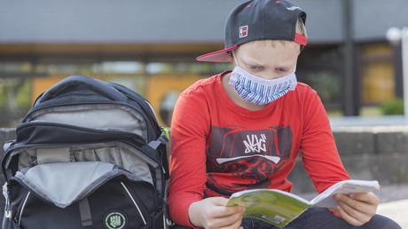 Ein Junge mit einer Maske sitzt auf dem Schulhof und liest etwas: In Bayern gilt nun zwei Wochen lang Maskenpflicht im Unterricht ab Klasse 5.