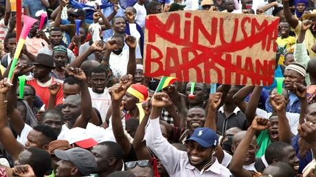 Ein Mann hält in Bamako, Mali, ein Transparent gegen die Multidimensional Integrated Stabilization Misiion in Mali (MINUSMA) der Vereinten Nationen. 21. August 2020.