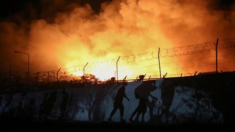 Flüchtlinge und Migranten, die ihre Habseligkeiten bei sich tragen, sind als Silhouette zu erkennen, als sie vor einem Feuer fliehen, das im Lager Moria auf der Insel Lesbos (Griechenland) brennt. 9. September 2020.
