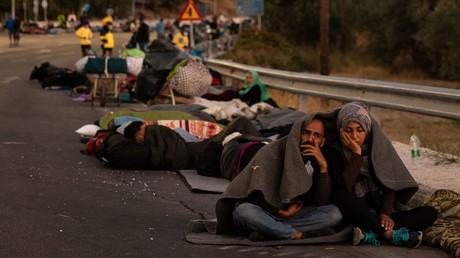 Ein Paar sitzt mit einer Decke zugedeckt, als Flüchtlinge und Migranten nach einem Brand im Lager Moria auf der griechischen Insel Lesbos an einer Straße lagern. 10. September 2020.
