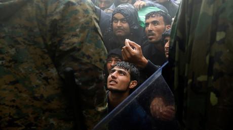 Migranten und Flüchtlinge bitten mazedonische Polizisten, während eines Regenschauers in der Nähe des griechischen Dorfes Idomeni die Grenze von Griechenland nach Mazedonien passieren zu dürfen. 10. September 2015.