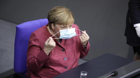 Symbolbild: Bundeskanzlerin Angela Merkel setzt sich im Bundestag eine Maske auf. (Berlin, 30. September 2020)