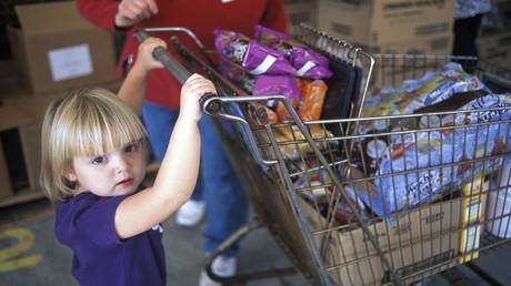 Ein kleines Mädchen schiebt einen Einkaufswagen bei der Lebensmittelbank in McArthur, Ohio, USA.