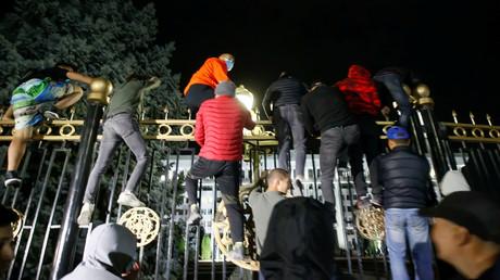 Demonstranten versuchen, während eines Protests gegen das Ergebnis der Parlamentswahlen auf das Gelände eines Regierungsgebäudes in Bischkek, Kirgisistan, zu gelangen.