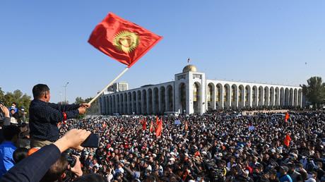 Während einer Kundgebung gegen die Ergebnisse der Parlamentswahlen in Bischkek, Kirgisistan, schwenkt ein Mann die kirgisische Flagge.