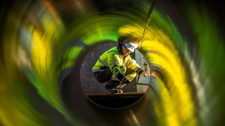 Ein Arbeiter steht im Hafen von Sassnitz-Mukran vor einer der tonnenschweren Röhren zur Fertigung der Erdgaspipeline Nord Stream 2