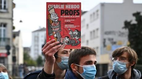 Ein Mann hält eine Ausgabe des Satiremagazins Charlie-Hebdo in die Höhe. Aufnahme während einer Demonstration in Rennes am 17. Oktober 2020, einen Tag nachdem ein Lehrer in Conflans-Sainte-Honorine, 30 Kilometer nordwestlich von Paris, von einem Angreifer ermordet wurde.