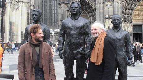 Der Künstler Davide Dormino mit John Shipton, dem Vater von Julian Paul Assange, vor dem Kölner Dom.