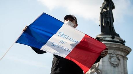 Ein Mann hält eine französische Fahne mit der Aufschrift