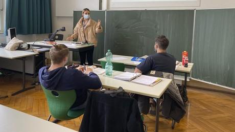 Eine Lehrerin mit dicker Winterjacke und Mund-Nasen-Schutz im Unterricht: Nach den Herbstferien müssen Schüler ab der 5. Klasse in Nordrhein-Westfalen auch an ihrem Sitzplatz wieder Maske tragen.