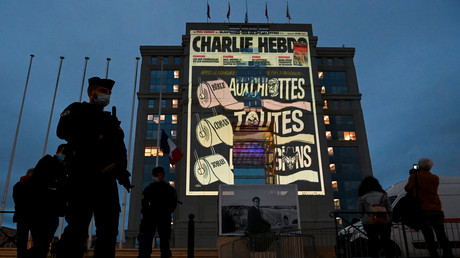 Polizeibeamte stehen Wache, während Karikaturen der französischen Satirezeitung Charlie Hebdo auf die Fassade des