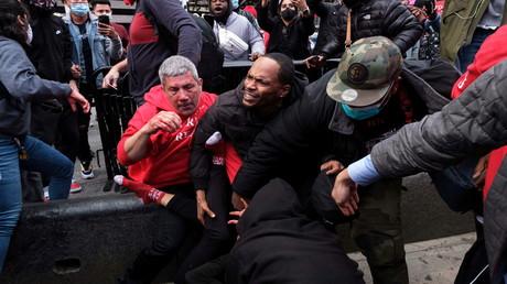 Ein Mann schützt nach Zusammenstößen in New York am 25. Oktober 2020 einen Unterstützer von US-Präsident Donald Trump vor Anti-Trump-Demonstranten.