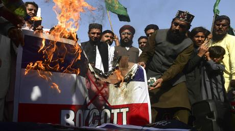 Sunnitische Muslime verbrennen in Karatschi eine französische Nationalflagge mit einem durchgestrichenen Bild des französischen Präsidenten Emmanuel Macron. 27. Oktober 2020.
