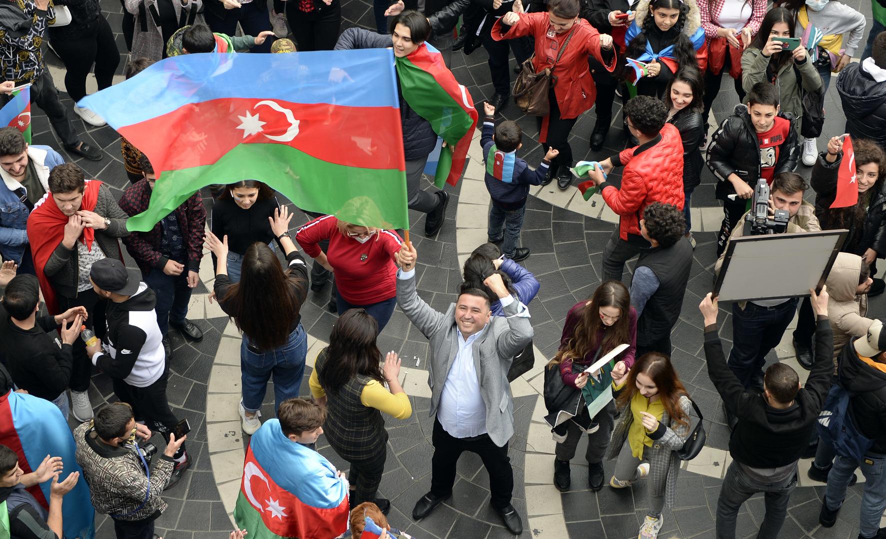 Aserbaidschaner halten ihre Nationalflagge hoch, während sie in den Straßen der Hauptstadt Baku feiern. 10. November 2020