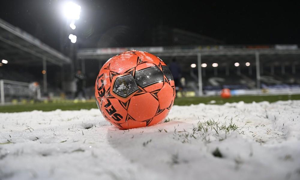 Weiß auf Weiß: Schnee auf Rasen macht Fußballspieler beinahe unsichtbar