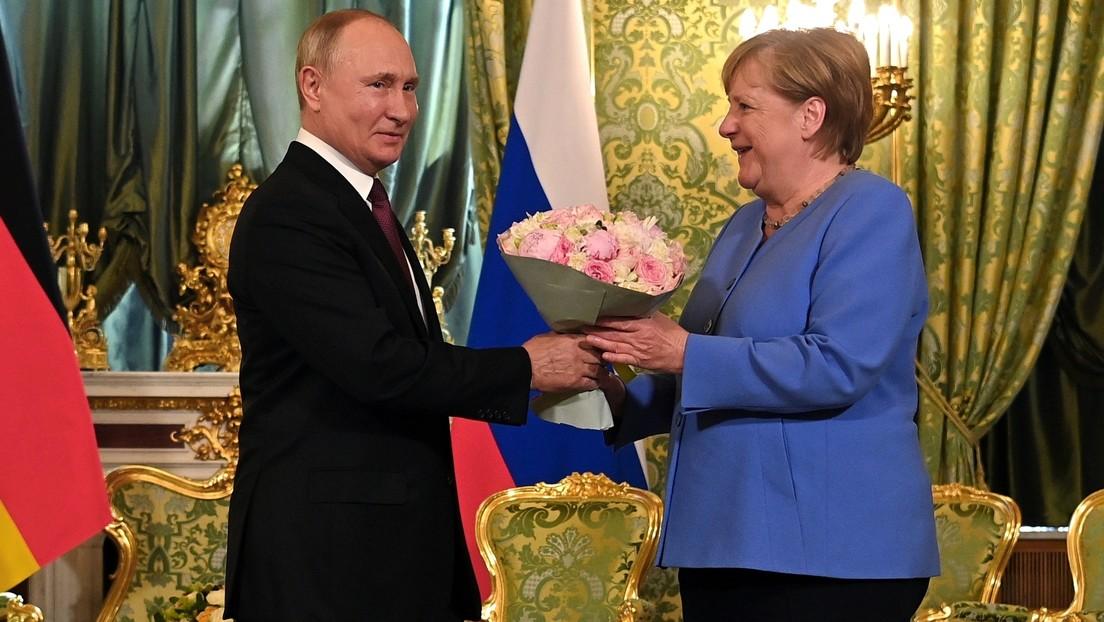 Kavalier der alten Schule: Wladimir Putin reicht deutscher Kollegin Angela Merkel Begrüßungsstrauß