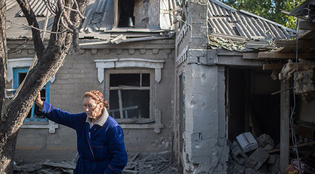 A woman stands by the house damaged during a mortar shelling in the village of Oleksandrivka, Donetsk Region. © Iliya Pitalev