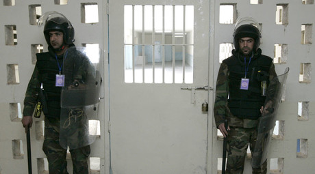 Guards stand guard at a gate in the Baghdad Central Prison in Baghdad's Abu Ghraib. © Mohammed Ameen