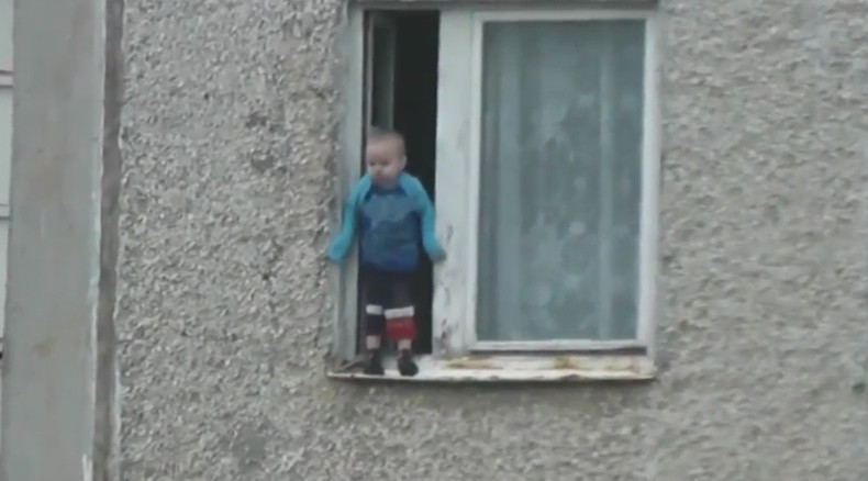 Worst parents ever? Russian toddler hangs out of 8th floor window (VIDEO)