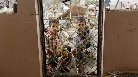 Boys look from behind window bars of a house damaged by a Saudi-led air strike in Yemen's capital Sanaa. © Khaled Abdullah