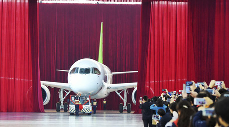 People take pictures and videos as the first C919 passenger jet made by the Commercial Aircraft Corp of China (Comac) is pulled out during a news conference at the company's factory in Shanghai, November 2, 2015. © Reuters