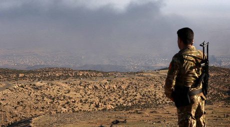 An Iraqi Kurdish fighter looks on as smoke billows during an operation by Iraqi Kurdish forces backed by US-led strikes in the northern Iraqi town of Sinjar, in the northern Iraqi province of Mosul, on November 12, 2015 © Safin Hamed