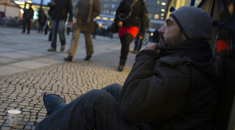 A homeless man begs for money at Alexanderplatz square in Berlin. © Thomas Peter