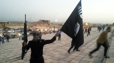 A fighter of the Islamic State  holds an ISIL flag and a weapon on a street in the city of Mosul. © Stringer