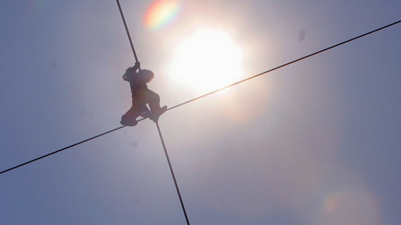 Soaring neighbor: Russian daredevil walks tightrope after laying 10-story-high wire (VIDEO)