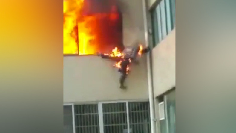 Firefighter in flames jumps out of window in Chinese apartment inferno (VIDEO)