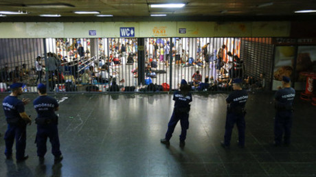 Hungarian police officers guard refugees at a makeshift camp in an underground station near the Keleti train station in Budapest, Hungary © Leonhard Foeger