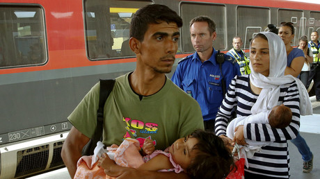 Migrants from Syria are accompanied by a Swiss police officer upon their arrival at the railway station in the north-eastern Swiss town of Buchs September 1, 2015. © Arnd Wiegmann