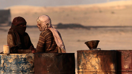 People talk as they stand next to oil barrels at a makeshift oil refinery site in al-Mansoura village in Raqqa's countryside © Hamid Khatib