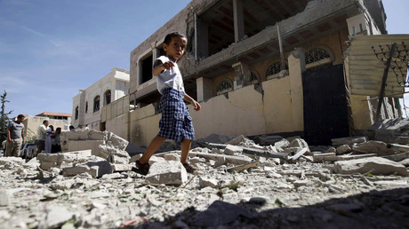 A boy walks past the a house damaged by a Saudi-led air strike in Yemen's capital Sanaa. © Mohamed al-Sayaghi