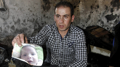 A relative of 18-month-old Palestinian baby Ali Dawabsheh, who was killed after his family's house was set to fire in a suspected attack by Jewish extremists, shows his picture at the burnt house in Duma village near the West Bank city of Nablus July 31, 2015 © Abed Omar Qusini