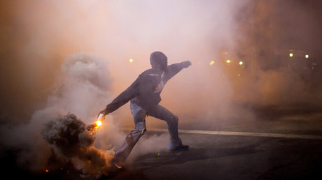A protester throws a gas canister back at police during clashes at North Ave and Pennsylvania Ave in Baltimore, Maryland April 28, 2015. © Eric Thayer