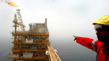 An Iranian man points to an oil production platform at the Soroush oil fields in the Persian Gulf, 1,250 km (776 miles) south of the capital Tehran © Raheb Homavandi CJF