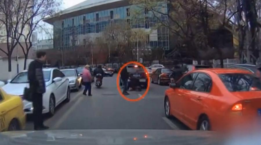 Angry biker kicks over jaywalker in China (VIDEO)